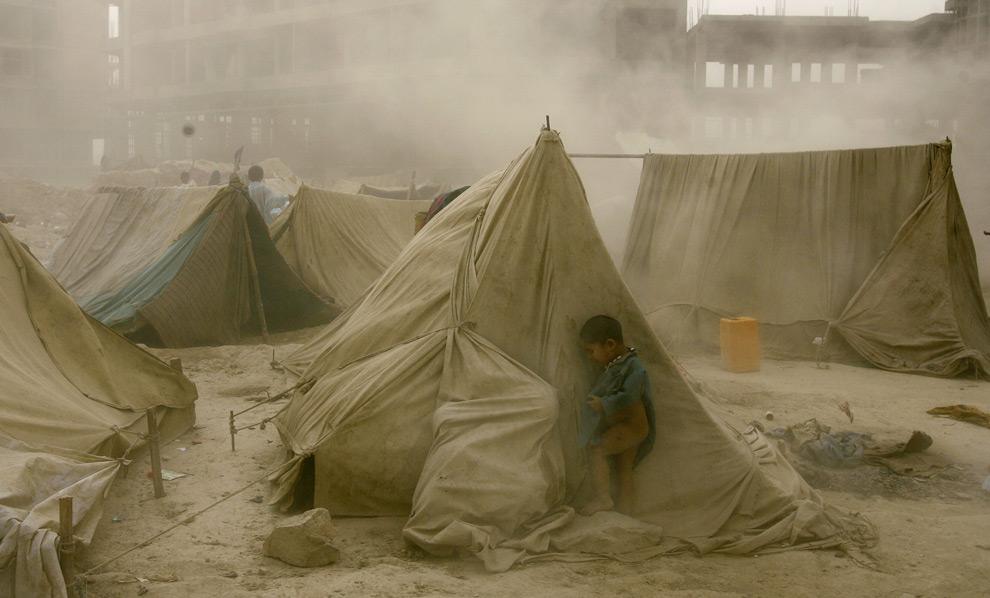 Афганский ребенок скрывается от шторма позади палатки в лагере беженцев в Кабуле. 7 октября 2008 год. MANPREET ROMANA/AFP/Getty Images