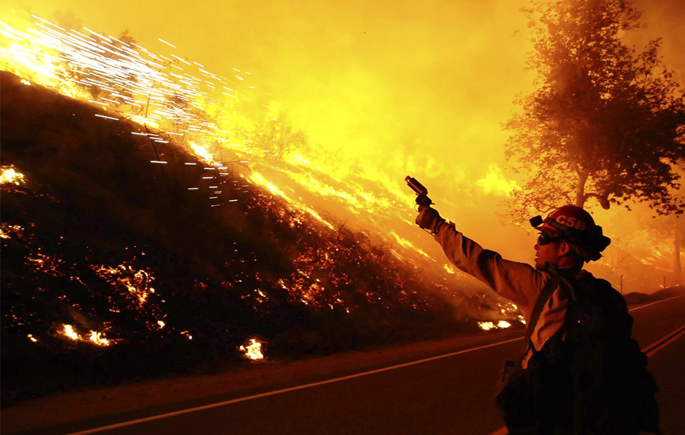 A firefighter uses a flare gun to set a backfire in the rugged area of Little Tujunga Canyon, 20 miles (32 km) north of downtown Los Angeles in the early hours of October 12, 2008. Fifty miles per hour gusty winds spread the fire towards ranches and houses in the heavily-forested canyon. (REUTERS/Gene Blevins)