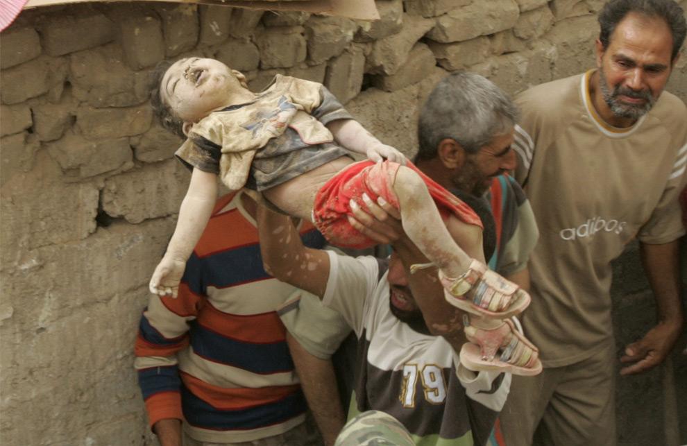 Человек несет тело ребенка из разрушенного дома после воздушного удара в городе Багдад. Ирак. 29 апреля 2008 год. REUTERS/Kareem Raheem