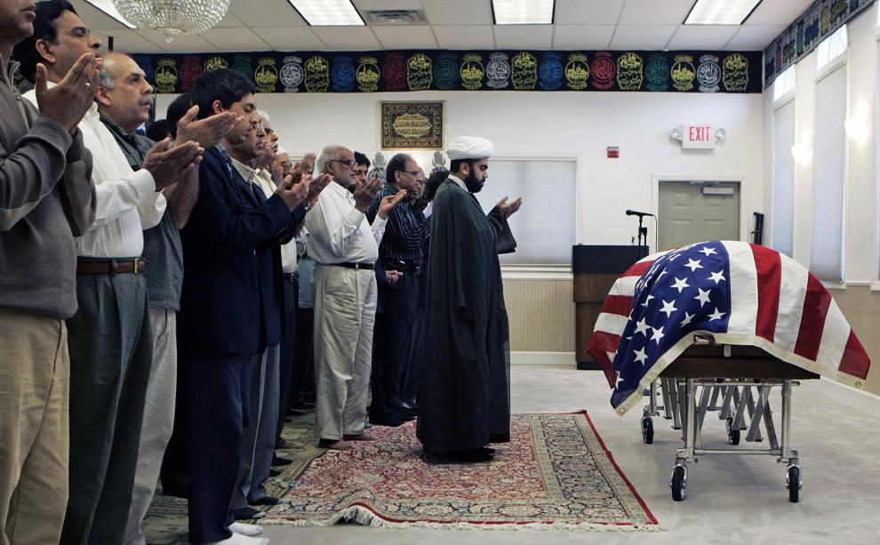 Имам Хашим Раза со скорбящими в молитве на похоронах Мохсина Накви-эль-Фатимы в Исламском центре в Нью-Йорке. Накви был мусульманином, уроженец Пакистана, он эмигрировал в США вместе со своей семьей в возрасте 8 лет, и стал гражданином США в 16, в последствии стал офицером армии США. Он был убит придорожной бомбой во время патрулирования в Афганистане. 22 сентября 2008. AP Photo/Mike Groll