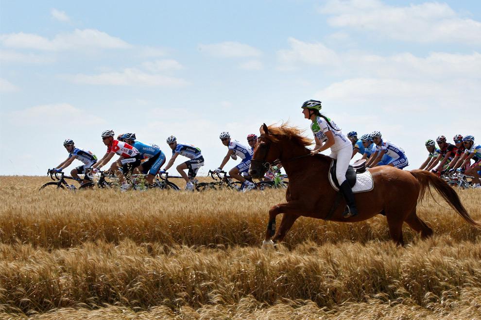 Женщина на коне идёт параллельно с велосипедистами на пятом этапе тур де франс в 2008 году. 9 июля 2008 год. Jasper Juinen/Getty Images