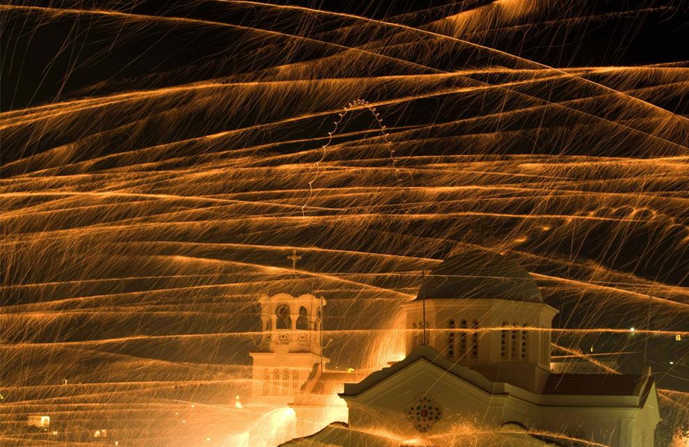 Ракеты пролетают над колокольней Айиос Маркос, греческой церкви, во время празднования православной Пасхи в восточной части Эгейского моря острова Хиос в Греции. 26 апреля 2008 год. REUTERS/Yiorgos Karahalis