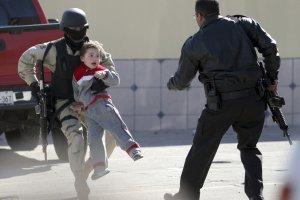 Полицейский уносит ребенка в ходе перестрелки в Тихуане. Калифорния. 17 января 2008 год. REUTERS/Jorge Duenes