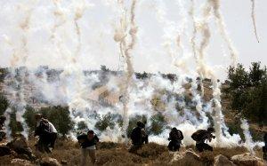 Слезоточивый газ запущенный израильскими солдатами падает c неба на палестинских и израильских мирных активистов, которые собрались для протеста против строительства барьера безопасности Израиля. 6 июня 2008 год. Abbas Momani/AFP/Getty Images
