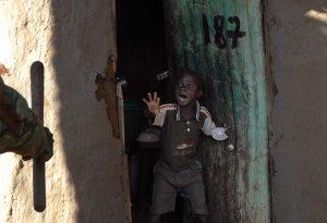 Кенийский мальчик кричит от испуга, поскольку он видит, что кенийский полицейский с жезлом приближается к двери его дома в трущобах Кибера, Найроби. 17 января 2008 год. WALTER ASTRADA/AFP/Getty Images