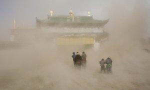 Этнические тибетские верующие идут через песчаную бурю к монастырю, чтобы встретить Монлам - Великий Молитвенный фестиваль. 17 февраля 2008 год. REUTERS/Reinhard Krause