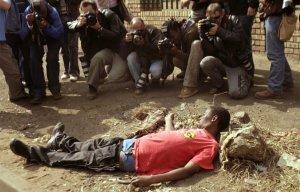 Фотографы снимают человека, раненного в ходе столкновений с южно-африканскими полицейскими, которые открыли огонь резиновыми пулями по сотням жителей трущоб, в конечном итоге были убиты более 60 человек и ранены сотни других. 20 мая 2008 год. REUTERS / Siphiwe СИБЕКО