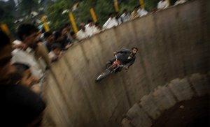Народ Пакистана смотрит как акробат едет по кругу на мотоцикле. 15 июня 2008 год. AP Photo/Emilio Morenatti