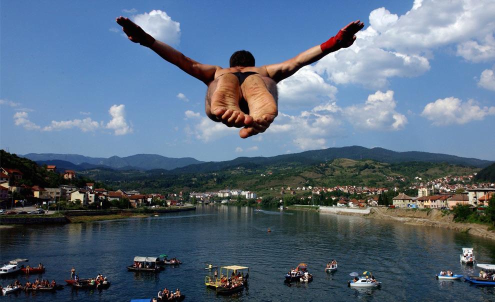 Спортсмен в ходе ежегодных соревнований по высотным прыжкам в воду, прыгает с высоты 14-ти метрового моста в реку Дрина в боснийском городе Вышеграде. 12 июля 2008 год. REUTERS/Stringer