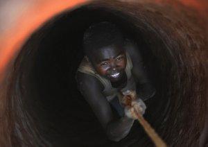 Молодой шахтёр спускается по верёвке в шахту по узкому проходу. Так работают шахтёры Мадагаскара в поисках сапфира. 14 сентября 2008 год. ROBERTO SCHMIDT/AFP/Getty Images