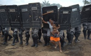 Женщина с ребёнком пытается устоять перед полицейскими, вытесняющими её с частных земель на окраине Манаус. Безземельные крестьяне безуспешно пытались сопротивляться выселению с луками и стрелами против полицейских, использующих слезоточивый газ и специально обученнных собак, в итоге крестьяне были изгнаны с земли. 11 марта 2008 год. REUTERS/Luiz Vasconcelos-A Critica/AE