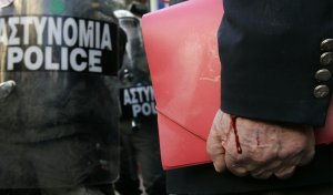 У мужчины по руке течёт кровь, он стоит перед беспорядками в Афинах, Греция. 9 декабря 2008 год. REUTERS/John Kolesidis