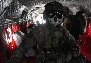 """Вертолётный стрелок армии США, его шлем окрашен в форму черепа. Он ждет солдат, которы располагаются на борту транспортного вертолета """"Чинук"""", восток Афганистана. Повстанцы Талибана напали на соседнюю заставу армии США, и американцы ответили автоматами, минометами и боевыми вертолетами. 30 октября 2008 год. John Moore/Getty Images"""