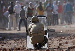Индийский полицейский защищается щитом от камней, которые бросают кашмирские мусульманские демонстранты в Сринагаре. Более двух десятков человек, в том числе 10 полицейских, получили ранения, когда в Кашмире полиция столкнулась с сотнями демонстрантов, бросающих камни, демонстранты были против индийского правления. 9 сентября 2008 год. Fayaz Aziz/Reuters
